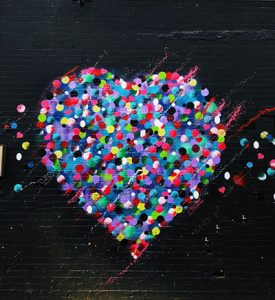 Graffiti image of a heart made up by many smaller, multi-colored hearts