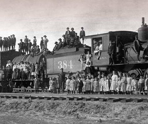 A historical image of a train with children standing on and around it